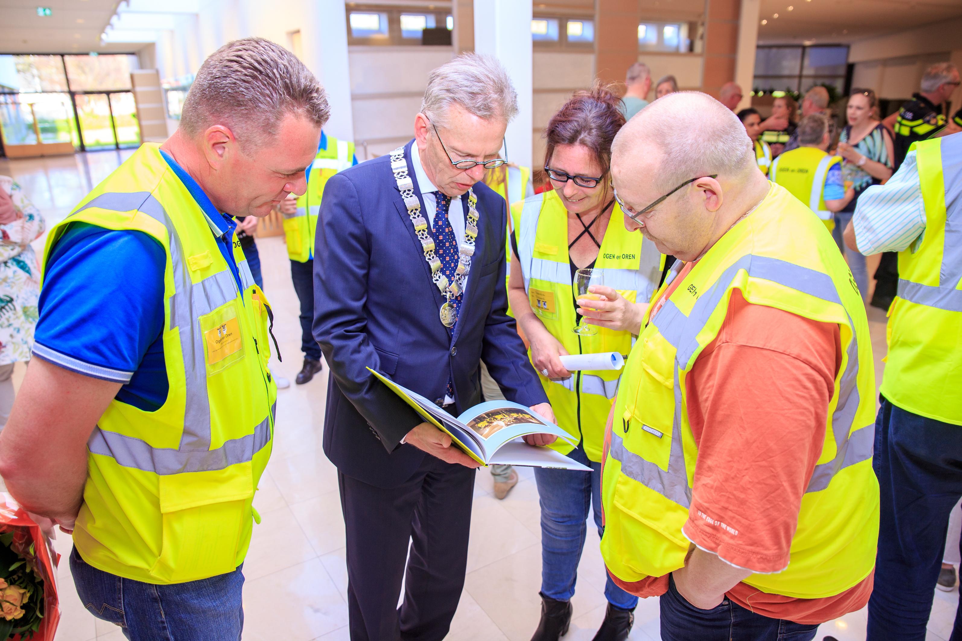 Coen Lageveen, een van de coördinatoren van Ogen en Oren, overhandigde het eerste jubileumboekje aan de burgemeester. (Foto: Gemeente Purmerend)