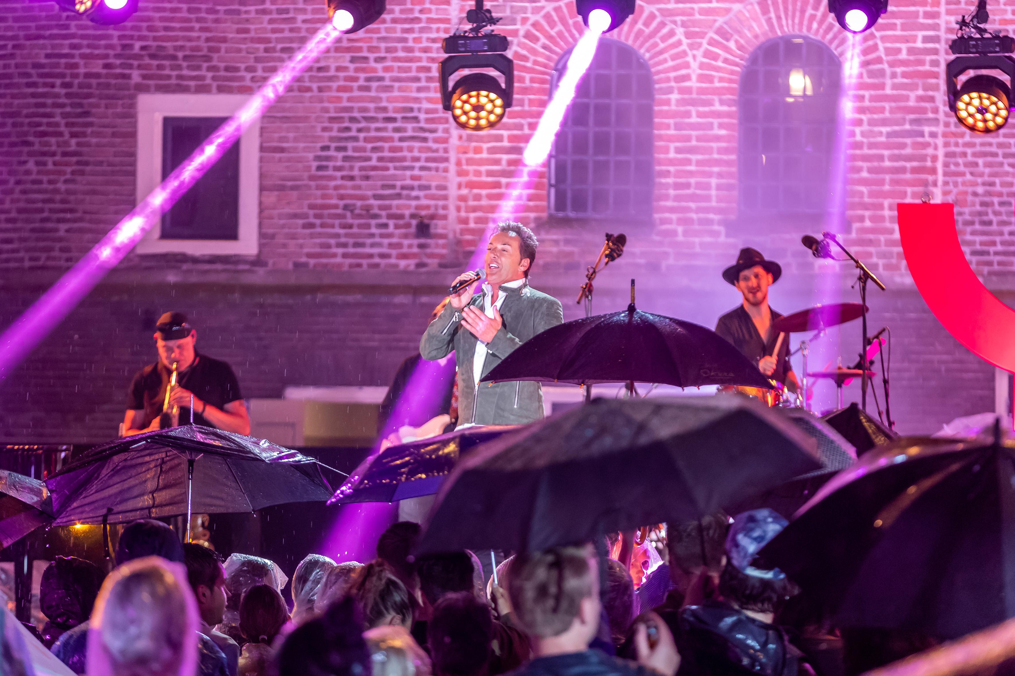 Boven de paraplu's treedt Gerard Joling op in 'Nederland staat op tegen kanker'. (Foto: Ed vd Pol)