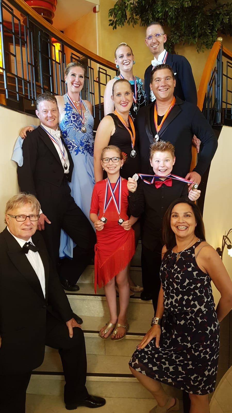 Op de voorgrond trotse trainers Cor & Bianca Valk met achter hun leerlingen en zeer blije prijswinnaars. (Foto: aangeleverd).
