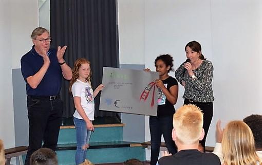 Twee leerlingen van groep 7, Jill van Braam en Janet Bendiboune, overhandigen de cheque aan Harry Jonk van Stichting Opkikker. De heer Jonk was zichtbaar ontroerd met dit mooie bedrag. (Foto: OBS De Delta)