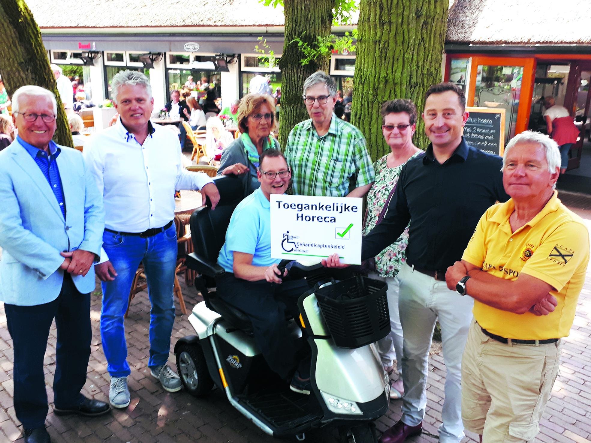 Wethouder Swart (l) en naast hem Edwin Steeman hebben het keurmerk overhandigd aan Theo Groentjes (tweede van rechts) temidden van de andere leden van het Platform Gehandicaptenbeleid. (foto aangeleverd)