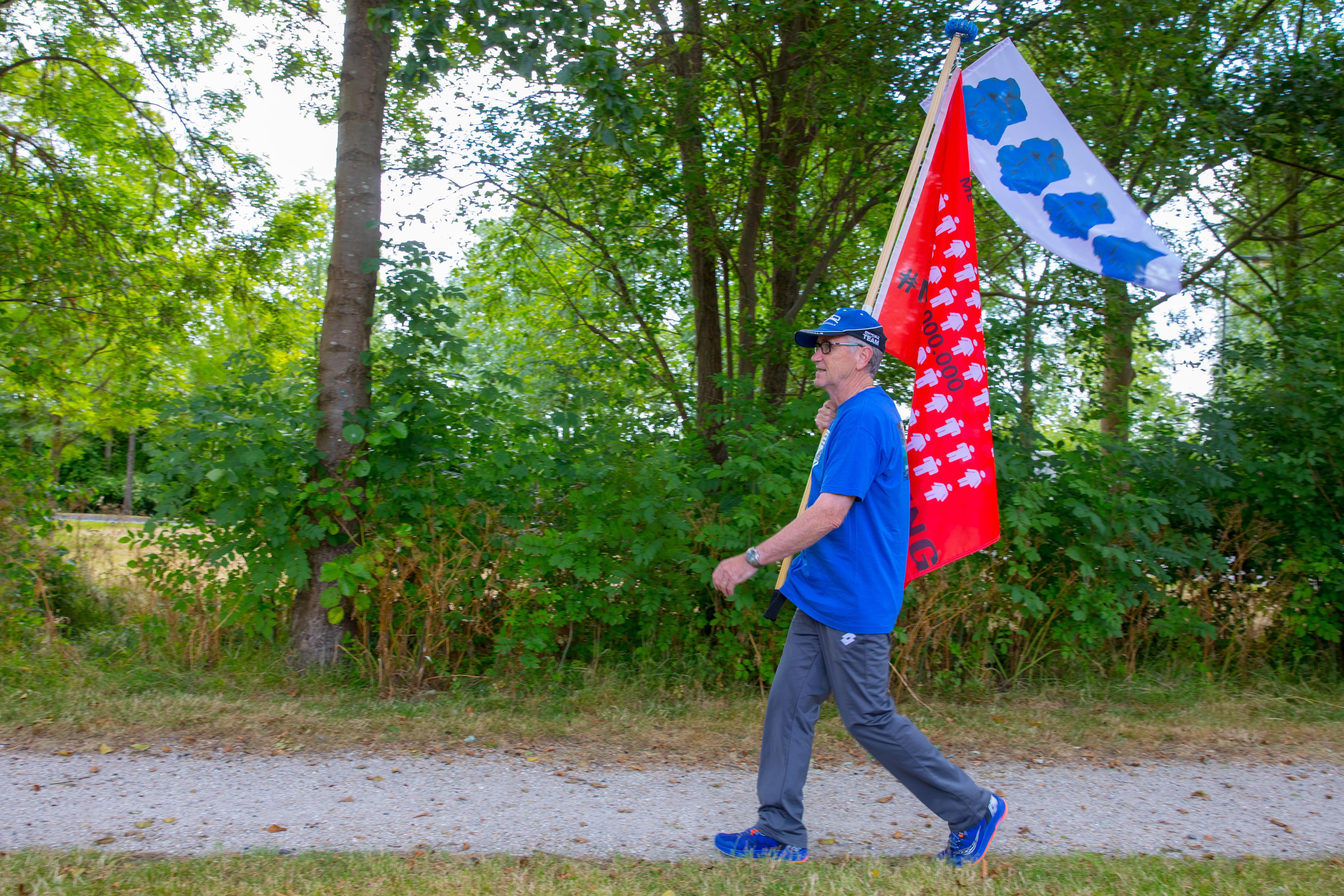 """René Robert loopt tijdens de Nijmeegse Vierdaagse mét de Millions Missing-vlag: """"Ik wil zoveel mogelijk aandacht vragen en geld ophalen voor de ziekte ME."""" (Foto: Vincent de Vries/RM)"""