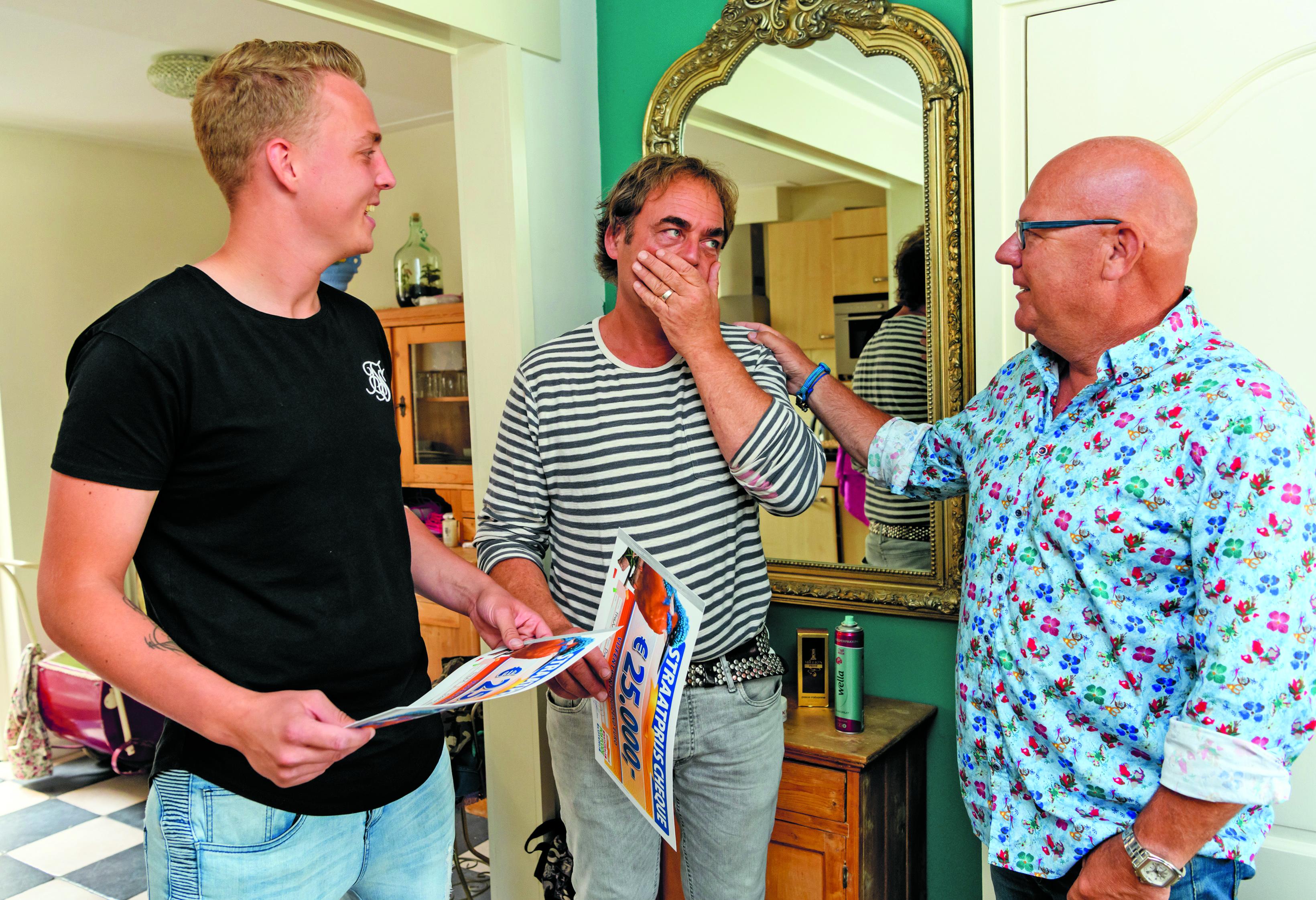 Vader Henk en zoon Liam worden beiden door Postcode Loterij-ambassadeur Gaston Starreveld verrast met een cheque van 25.000 euro. (Foto: aangeleverd)