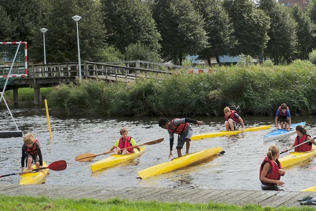 De deelnemers van de kanovakantieclub proberen in hun kano te staan. (Foto: Kanovereniging Viking)