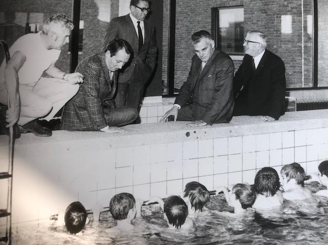 Links Chef zweminstructeur Piet Groot, wethouder Klaas Muije. staand Directeur Verkroost van zwembad 'De Schots'. Zittend Dhr. Kousbroek lid van stichtingbestuur en Jac P Schotman directeur Sport en Jeugdzaken.     (Foto: aangeleverd)