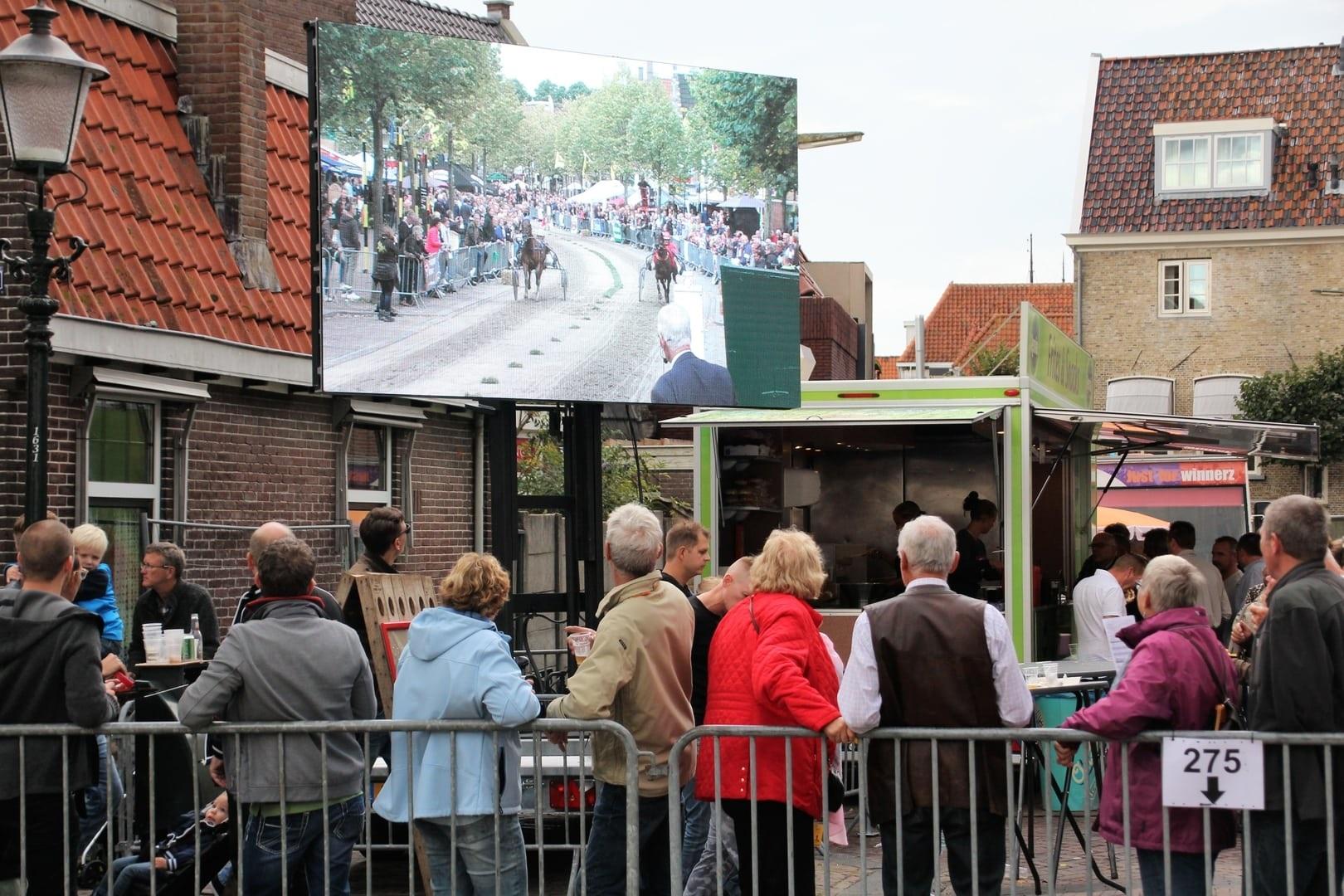 Bezoekers van de harddraverij in Medemblik volgen de hele koers live en op scherm. (Foto: aangeleverd)