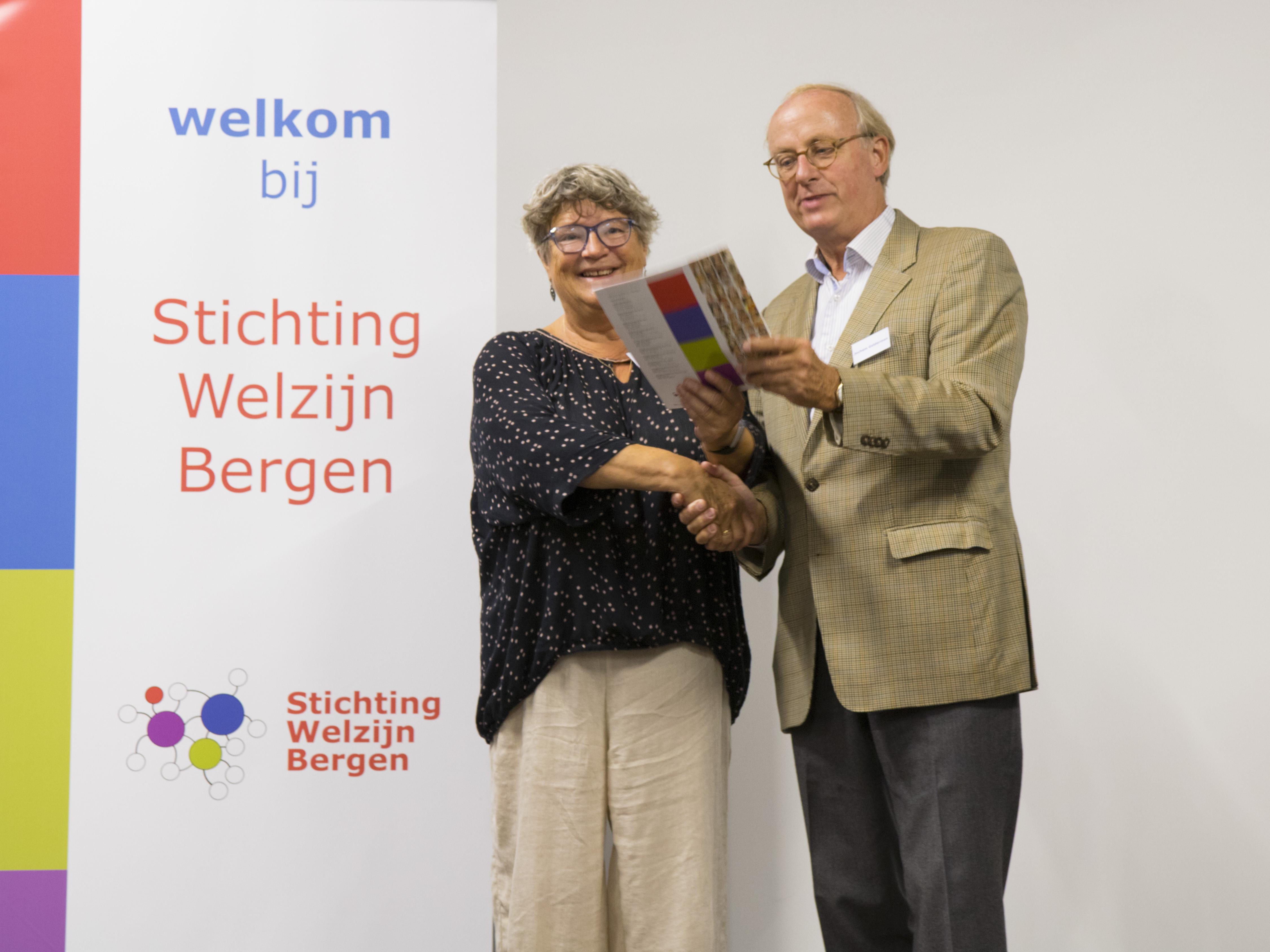 Renske de Vreede ontving het eerste exemplaar 'Wij zijn' van Stichting Welzijn Bergen uit handen van Jochem Gelderman. (Foto: aangeleverd).