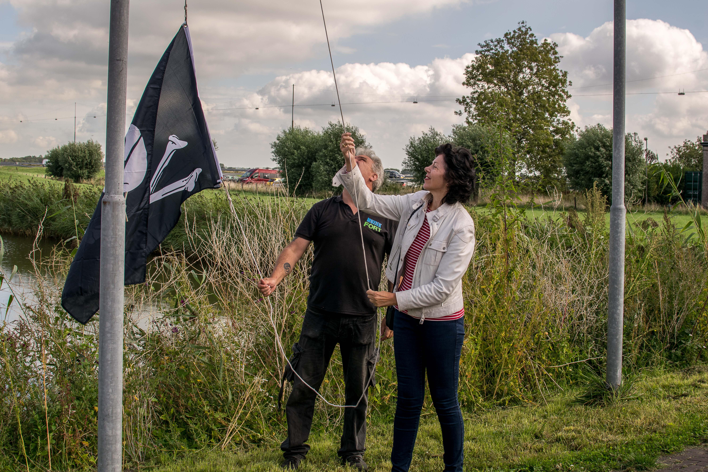 Wethouder Hanneke Niele helpt met het hijsen van de piratenvlag. (Foto: Aangeleverd)
