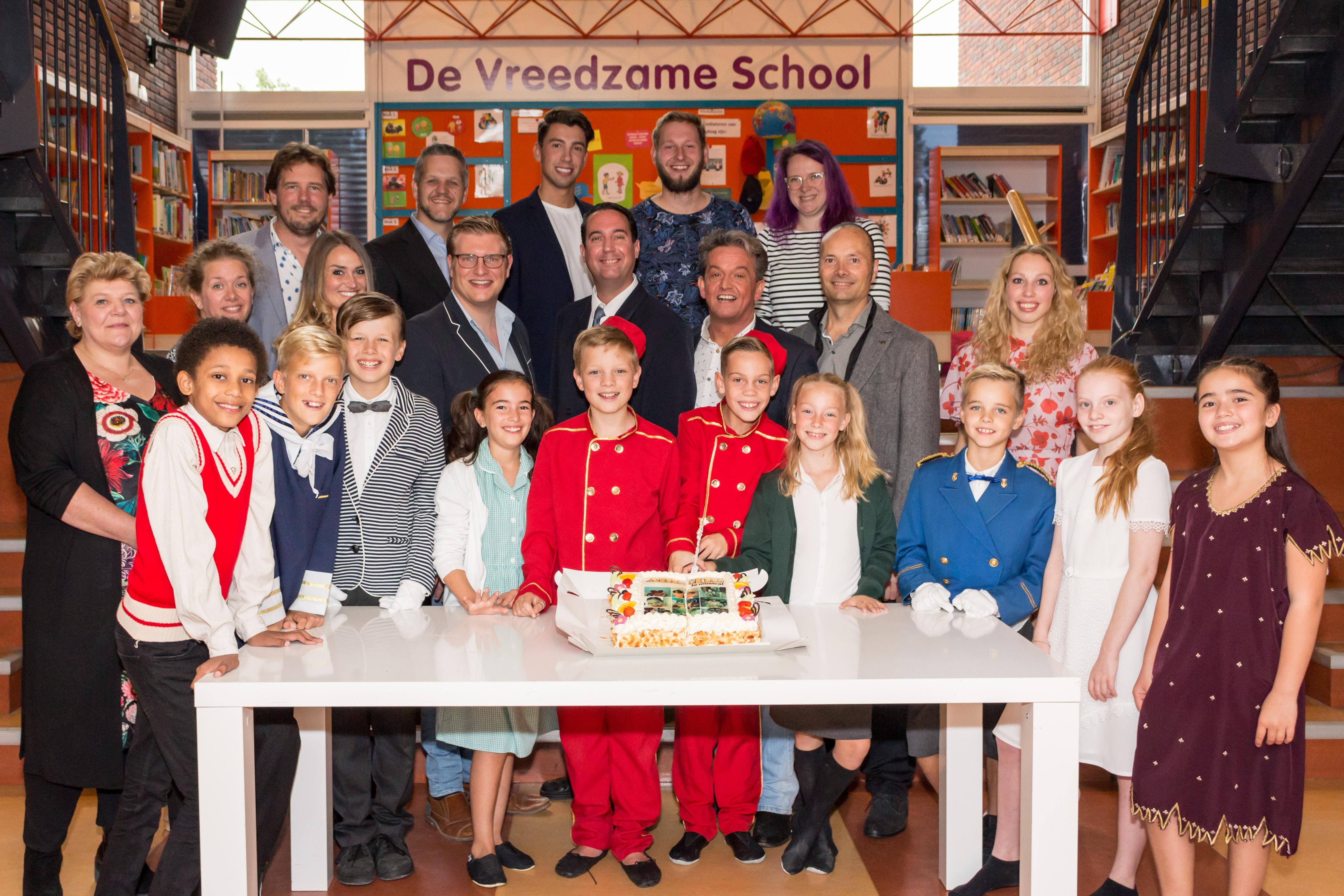 De volwassen- en een deel van de kindercast van Kids with Attitude snijden de taart aan van 'Abeltje de Musical'. (foto AvdK Fotografie)