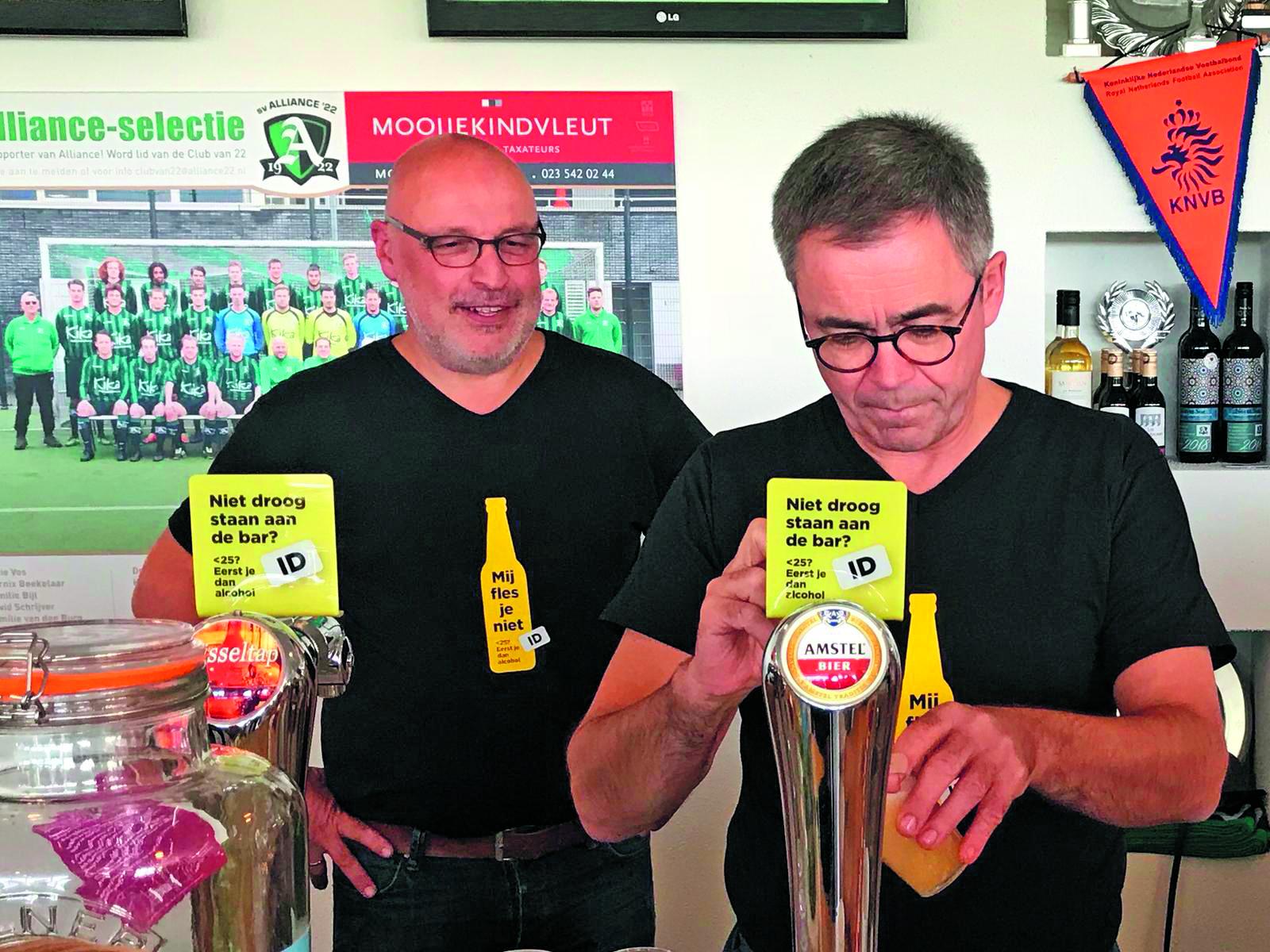 Onder toeziend oog van een barvrijwilliger, tapt burgemeester Jos Wienen (rechts) een biertje. (foto aangeleverd)