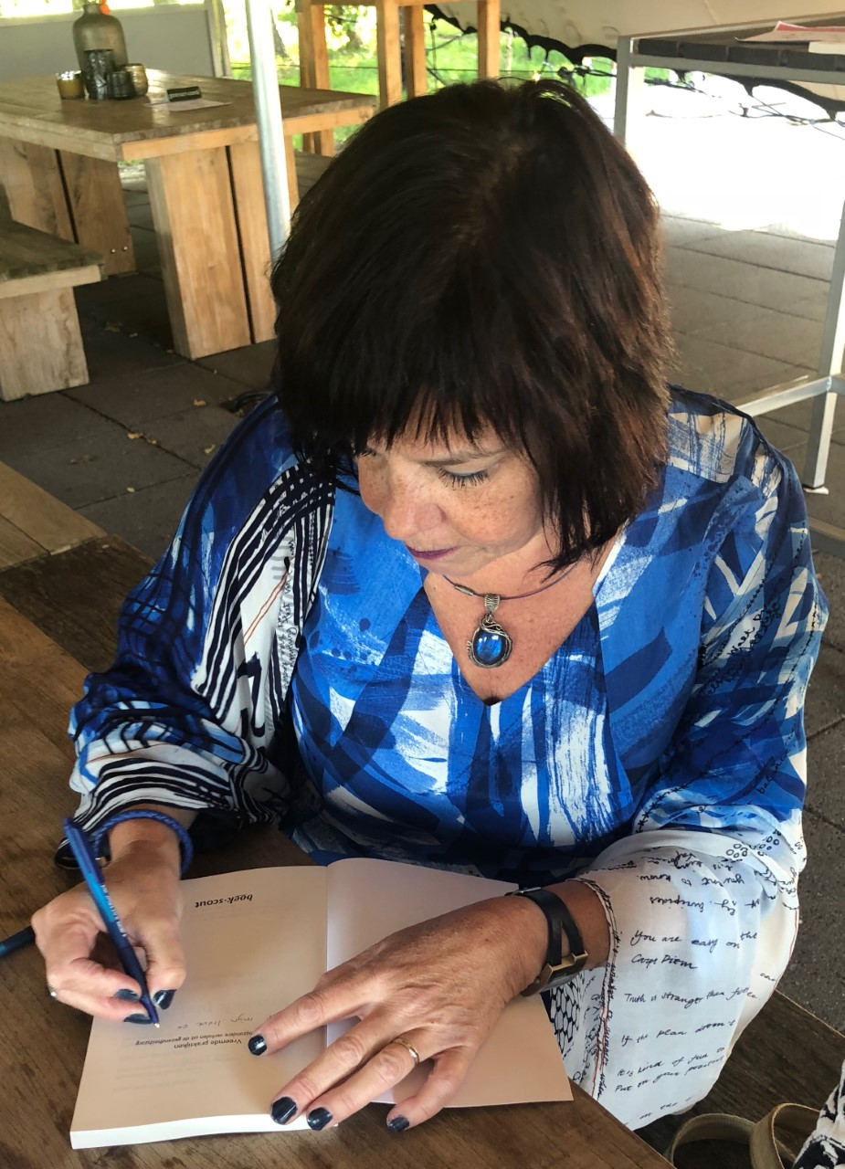Isa Bron signeert een van haar boeken. (Foto: aangeleverd)