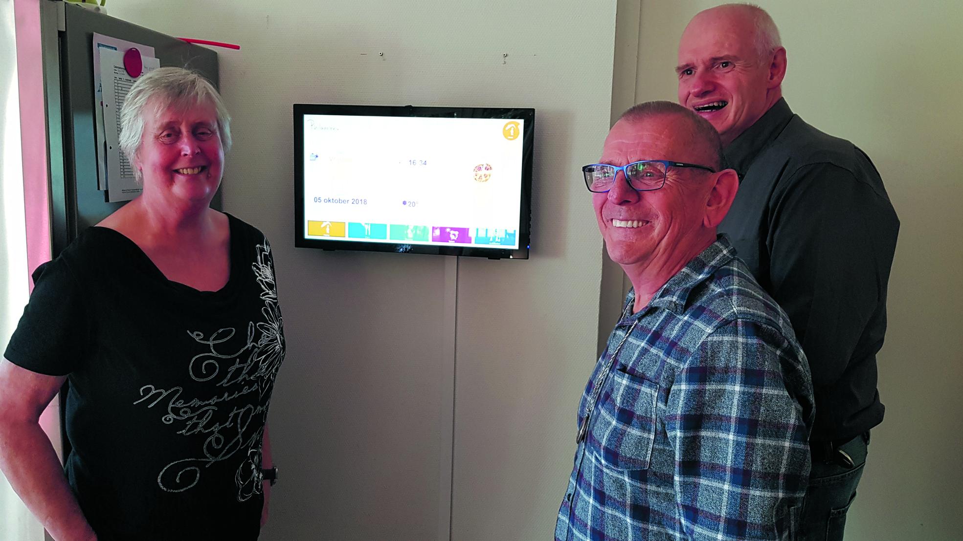 De bewoners Marjan, Gerrit en Pieter (vlnr) zijn inmiddels gewend aan het digitale bord. (foto Rodi Media)