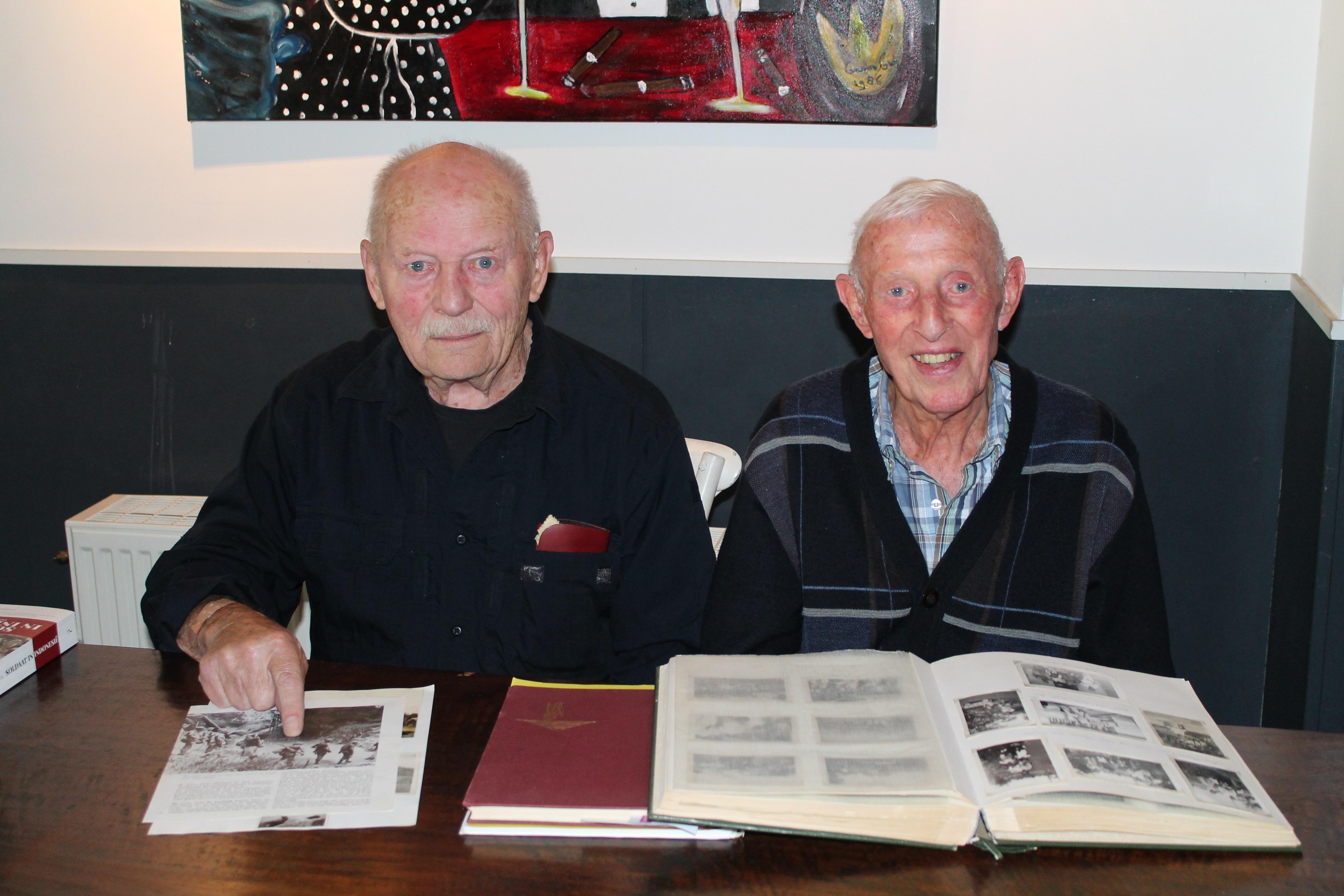 De heer Veldhoen en heer Stiemer laten foto's zien van vroeger. (Foto: Rodi Media/SZ)