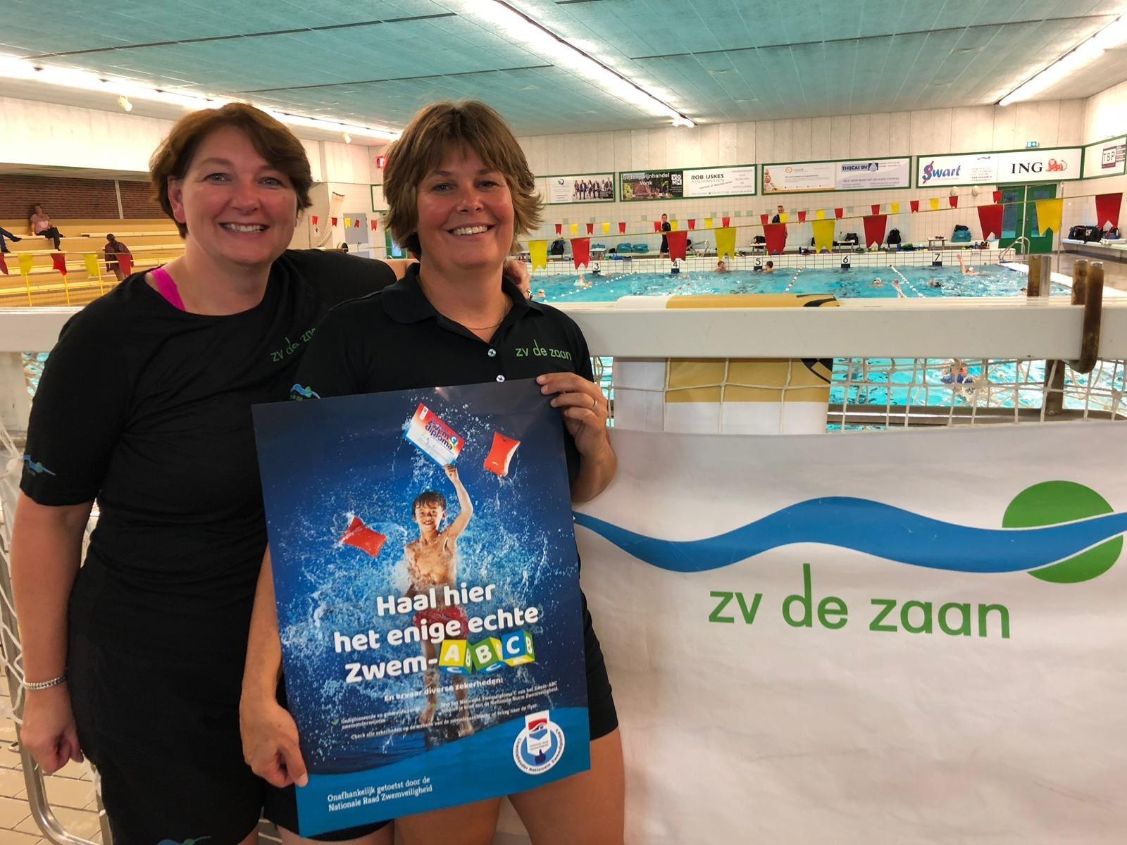 Judith Abcouwer (links) en Deborah de Lange (rechts) nemen de Licentie Nationale Zwemdiploma's in ontvangst. (Foto: ZV De Zaan)