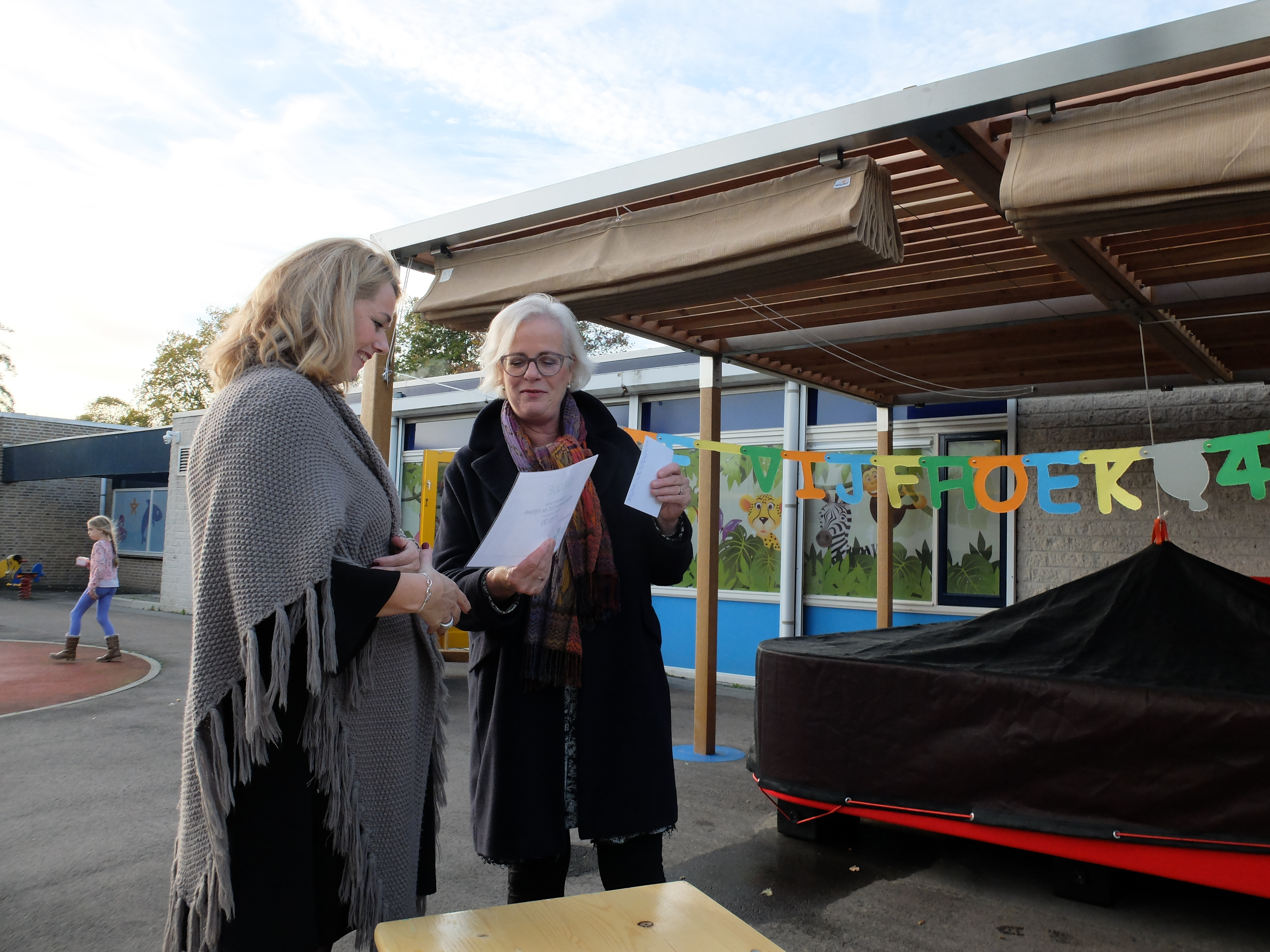 Teamleider Angelique Besseling van De Waerden (l) ontvangt een jubileumcadeau namens de gemeente Heiloo van wethouder jeugdzorg Elly Beens. (Foto: aangeleverd)
