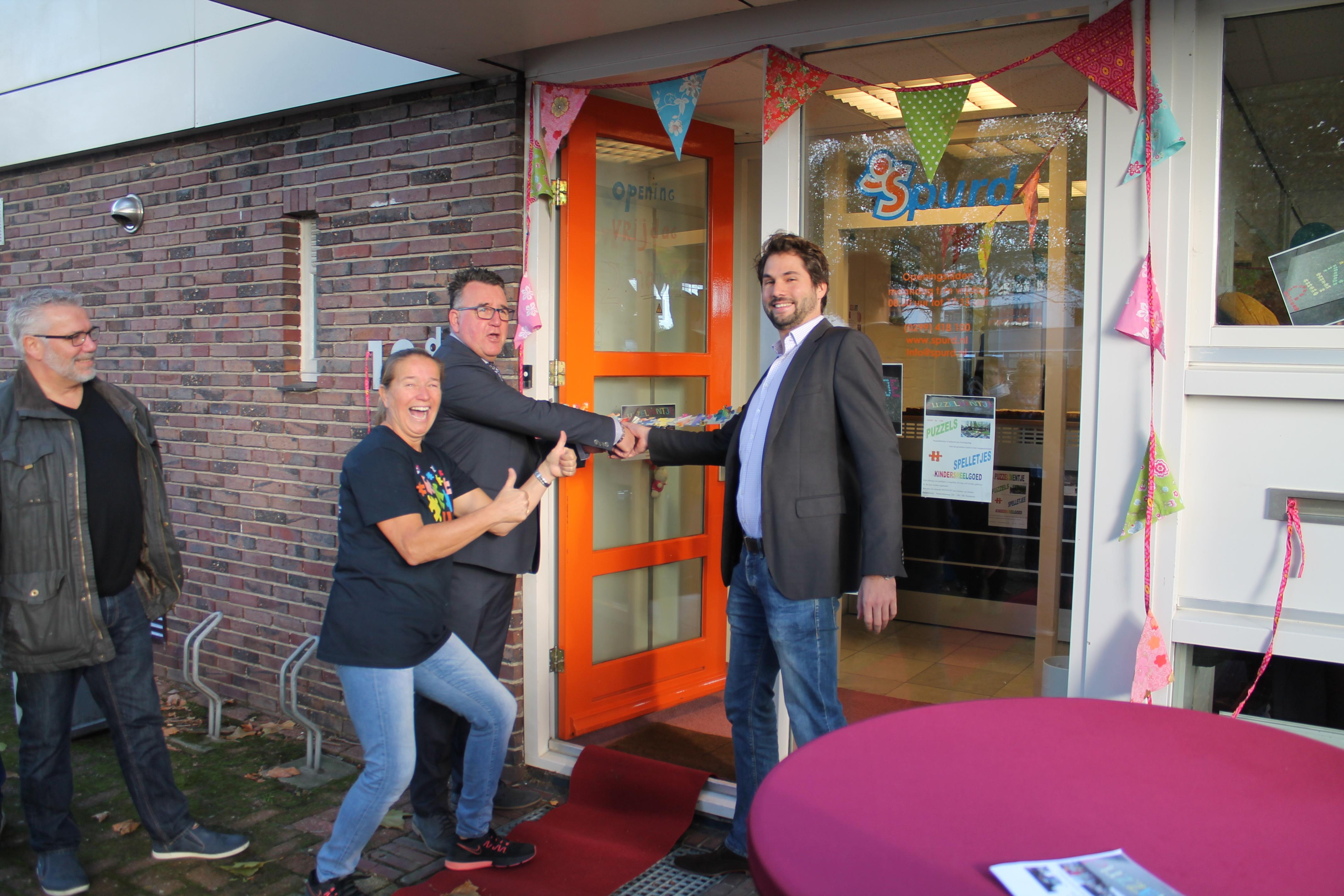 Gerdien van Delden (tweede van links) kijkt tevreden toe hoe Thijs Kroese en Mario Hegger de winkel openen. (Foto: RM/Michael Brouwers)