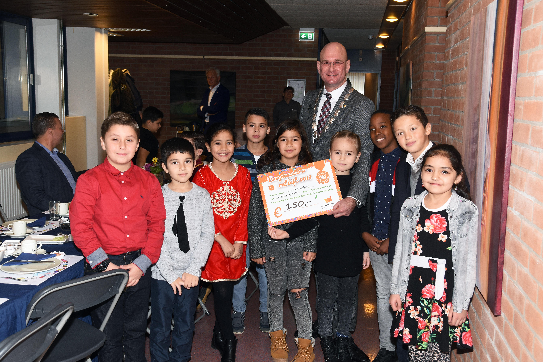 Na het ontbijt ontvingen de leerlingen uit handen van burgemeester Jan Nieuwenburg een cheque voor de Stichting Kinderpostzegels. (Foto: aangeleverd)
