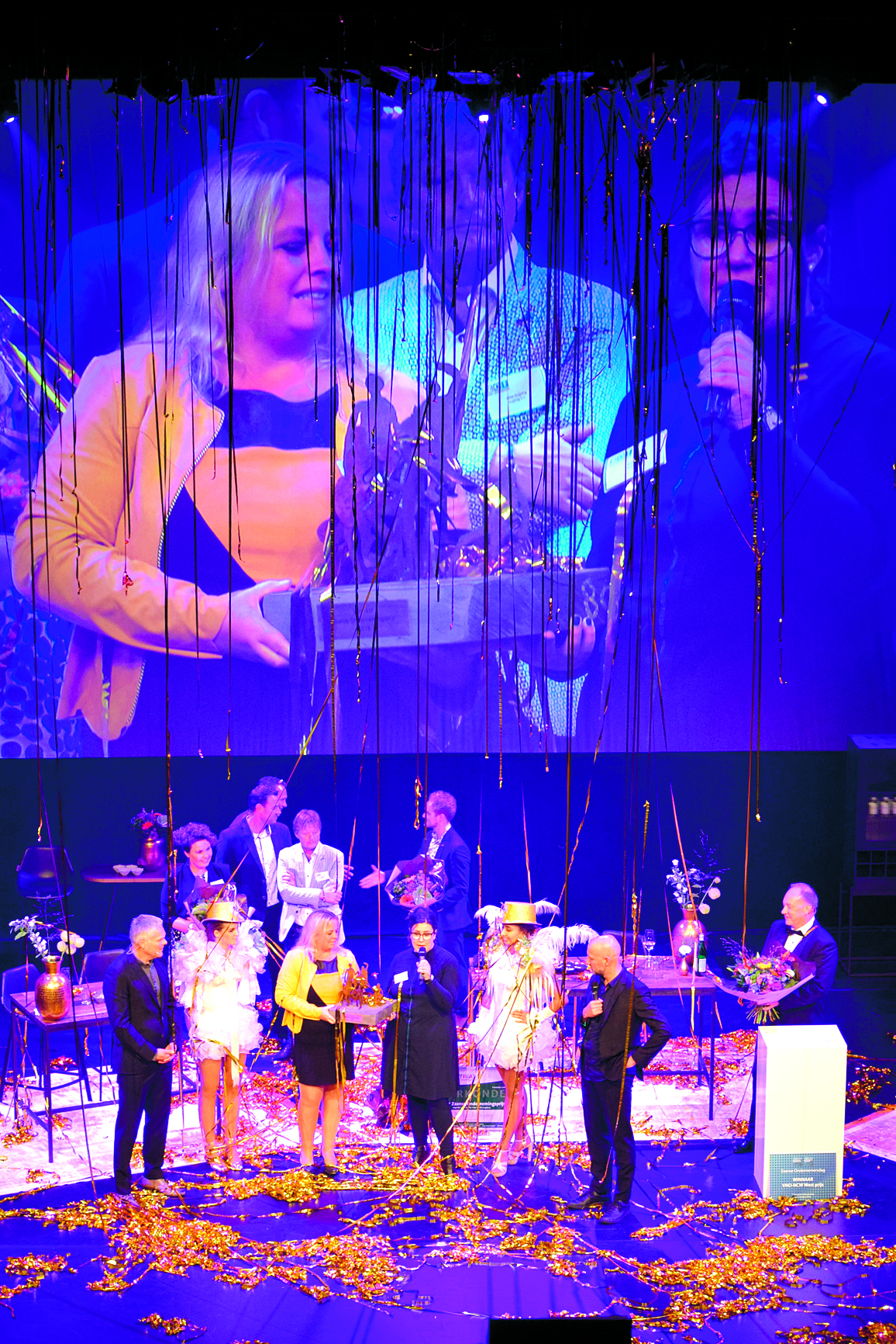 Winnaars Directeur Mandy Beets (met microfoon) en manager tussen de feestslingers. (Foto: YvdD/RM)