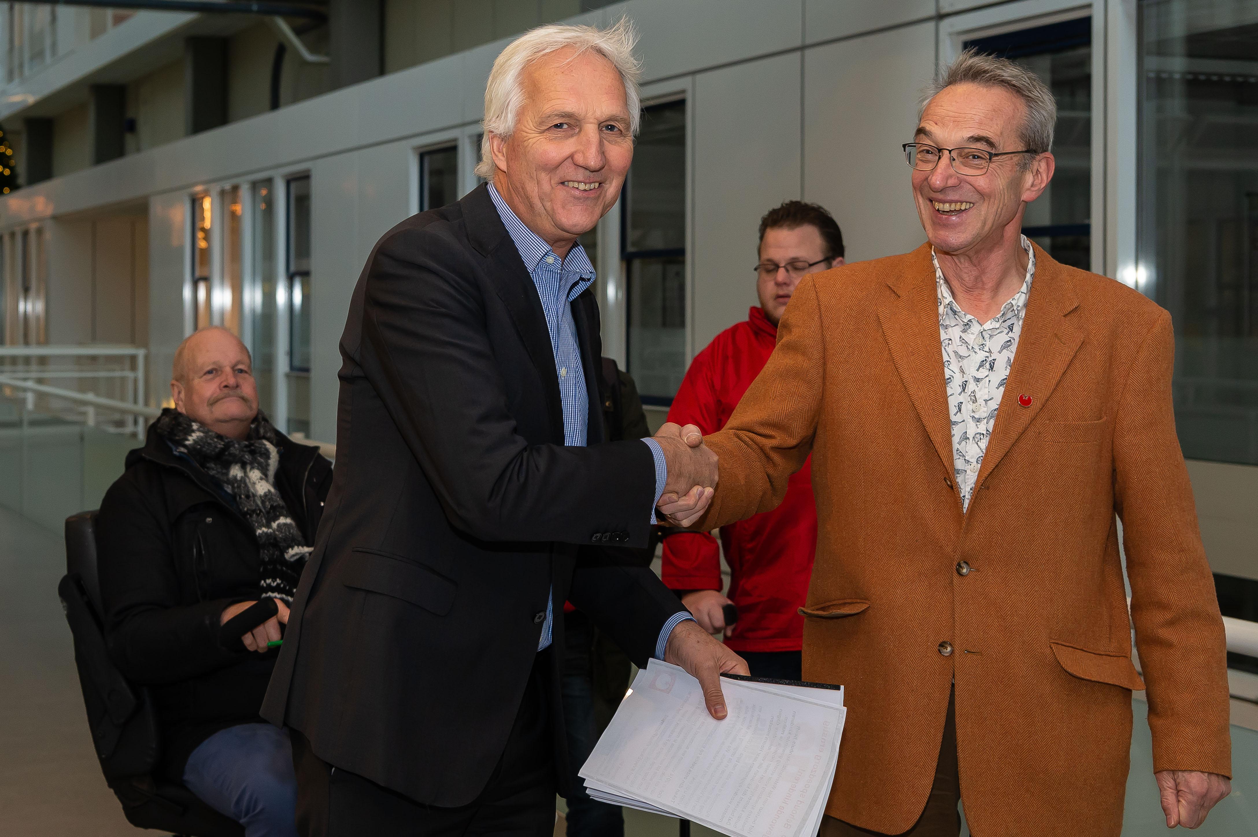 Arno Timmermans (Raad van Bestuur) neemt de petitie in ontvangst van SP's Wim Wildschut. (Foto: Han Giskes)