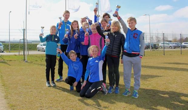 De jonge prijswinnaars van Voorne Atletiek bijeen met de behaalde trofeën.