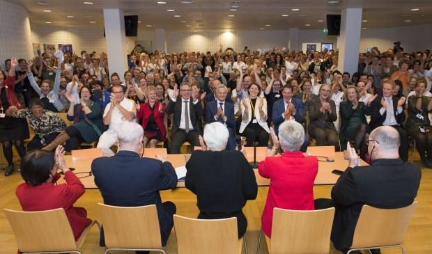 Een volle zaal met medewerkers reageert uitgelaten op het moment dat de positieve uitslag bekend wordt gemaakt.