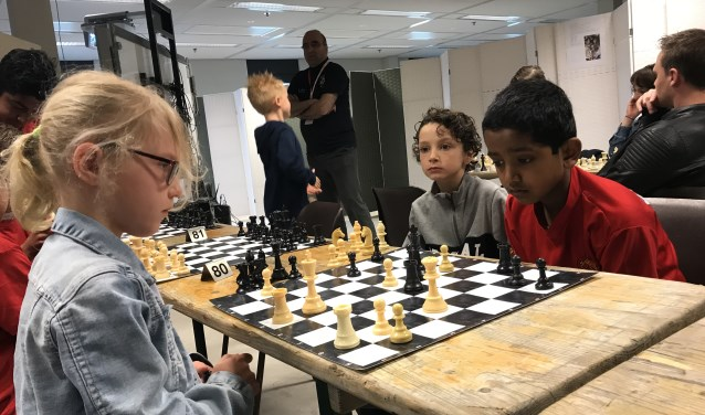 De jonge schakers zijn al druk voor de opening van het toernooi bezig.