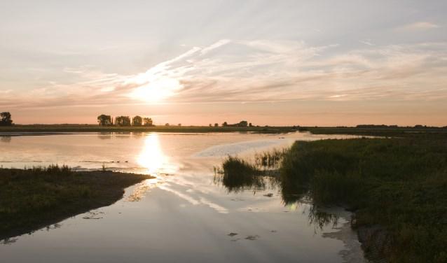 De zon zien wegzakken boven het weerspiegelende water. Ervaar de schoonheid van de natuur.