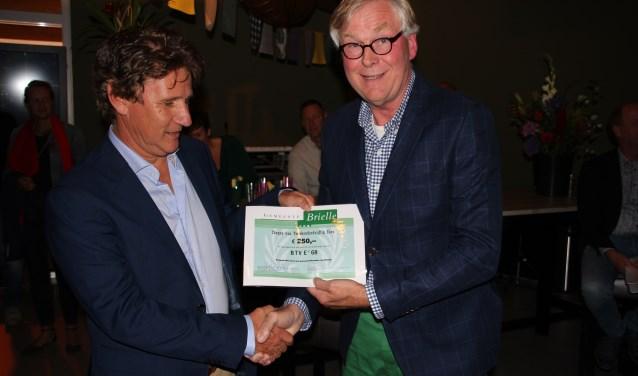 Voorzitter Frank Abrahams wordt gefeliciteerd door wethouder André Schoon en ontvangt een jubileumcheque van de gemeente Brielle