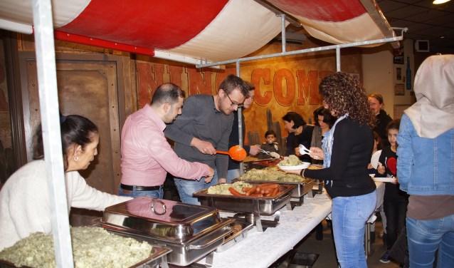 Het eten werd verzorgd door Hussam Karkas (in roze overhemd) met zijn vrouw, die drie jaar geleden vanuit Syrië naar Nederland kwamen. Hij gaat trouwens aan de slag als kok in het restaurant van WSW Ouddorp.