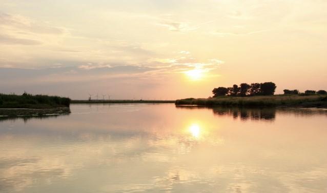 Varen in de schemering rond het natuureiland Tiengemeten. De zon zien wegzakken boven het weerspiegelende water.