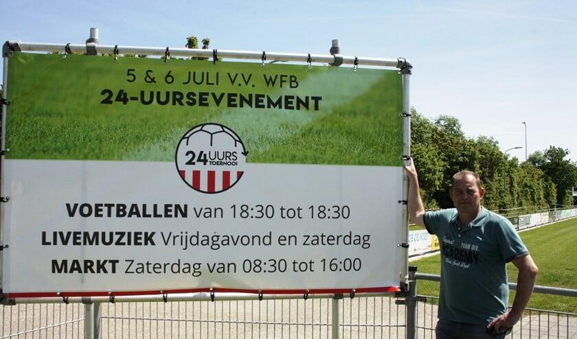 Leon Struijk, één van de organisatoren, bij het reclamebord van het 24-uurs toernooi.
