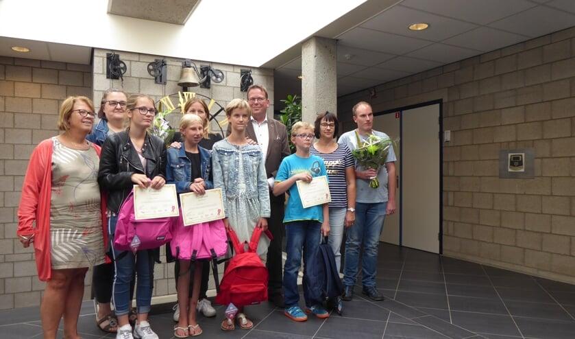 De trotse gecertificeerden van de Reiskoffer samen op de foto met ouders. verzorgers, vrijwilligers, opleiders en de wethouder.