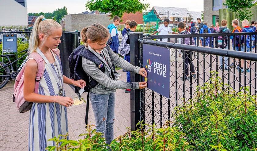Eva en Senna plakten de door de Vlasbloem  verdiende stickers op de High Five tegel.