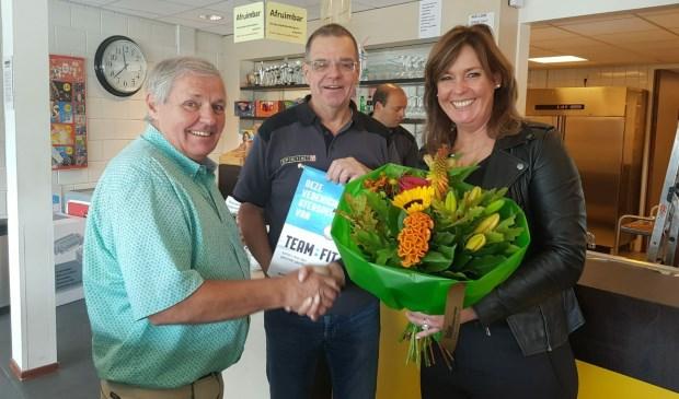 Henk van den Biggelaar (midden) en accommodatiemanager Johan de Koning (links) krijgen het zilveren vaantje uitgereikt van Karin Potting