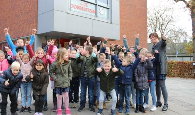Directrice Hanneke Meulblok (rechts) met leerlingen op het plein van de jarige school