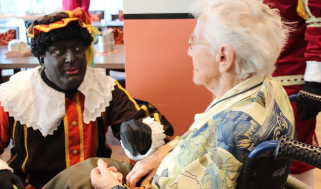 Piet geeft pepernoten aan een 100-jarige inwoner van De Vossemeren in Nieuw-Vossemeer