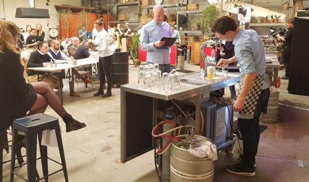 Een deelnemer tapt een biertje onder toeziend oog van de jury