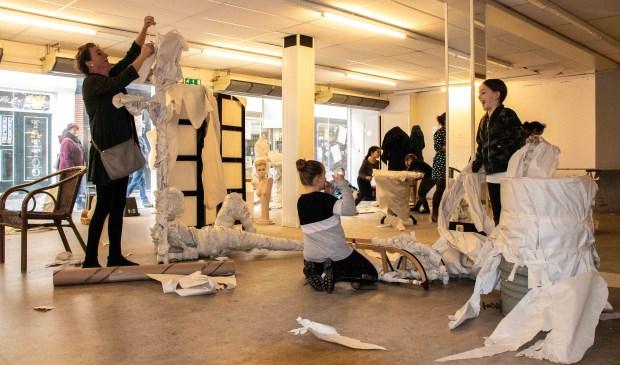 Leerlingen van de Frans Naereboutschool geven meubels een kunstzinnig jasje, met behulp van kunstenares Agnes den Hartogh (l).
