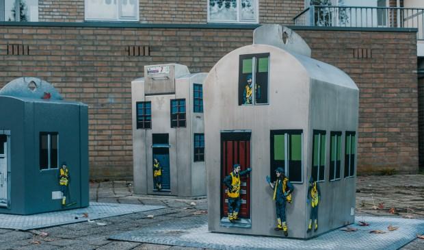 De tot huisjes omgetoverde afvalbakken die op verschillende plaatsen verschijnen.