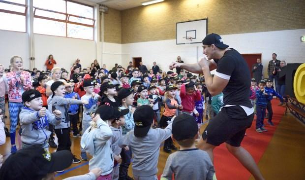 Jong en ouder doet mee aan de les van kickbokser Rico Verhoeven.