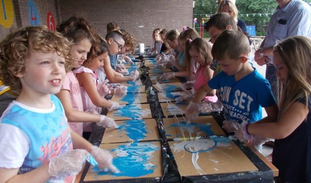Leerlingen leven zich uit tijdens een schilderworkshop.