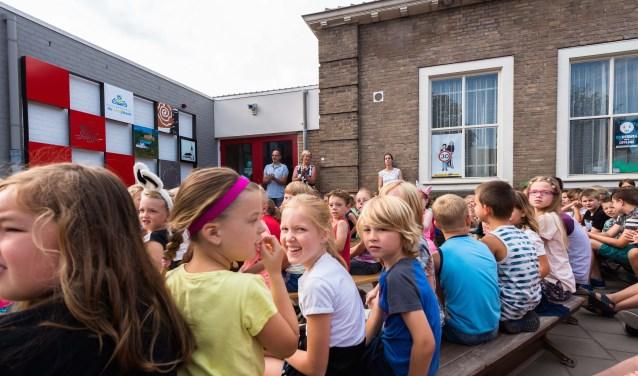 Kinderen kijken naar de onthulling van het kunstwerk. FOTO CORINE ROKS