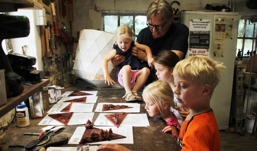 Léon Vermunt staat met de kinderen naar de net gemaakte puzzelstukjes  die op de oude sok komen te staan te kijken.