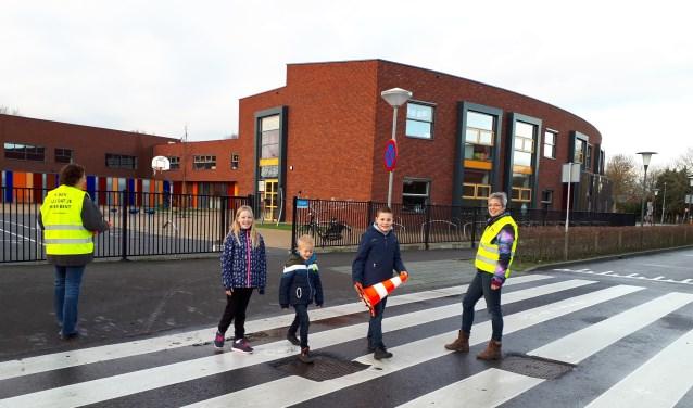 Verkeersouders Heidi de Jong (l) en Jeanet Steenbeek helpen kinderen met oversteken.