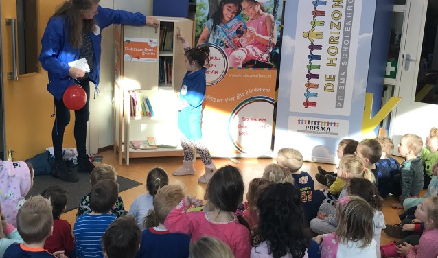 De jarige Ruhmen mag helpen met de opening van het kinderzwerfboekenstation.