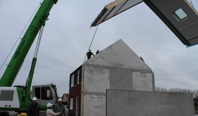 Wethouder Baartmans helpt bij het plaatsen van een dakelement op de 0 op de meter woningen aan de Lunet in Steenbergen