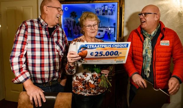 Nico en zijn vrouw Annie uit Roosendaal werden verrast door Postcode Loterij-ambassadeur Gaston Starreveld met de PostcodeStraatprijs-cheque.