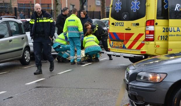 De scooterrijder wordt in de ambulance behandeld.