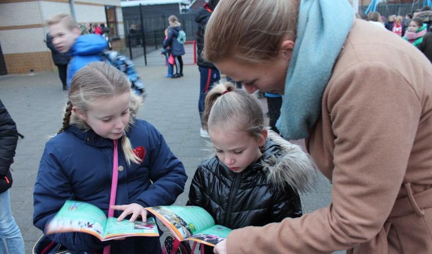 Wethouder Esther Prent neemt met een paar basisschoolleerlingen het boekje Sjors Sportief & Sjors Creatief door.