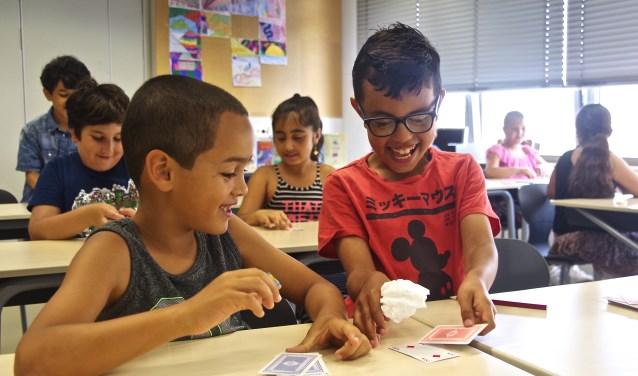 Twee jongens, die beiden Zacharias heten, genieten van een kaartspel. FOTO BO VAN SCHEYEN